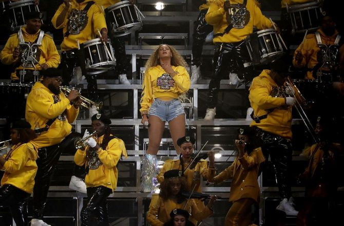 Beyonce surrounding by drum line band. All dawning yellow and berets.